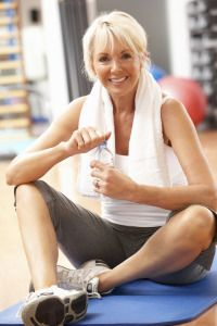 Senior Woman Resting After Exercises In Gym