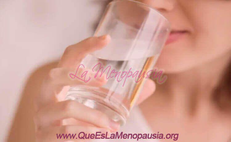 Mujer con sequedad bucal tomando agua
